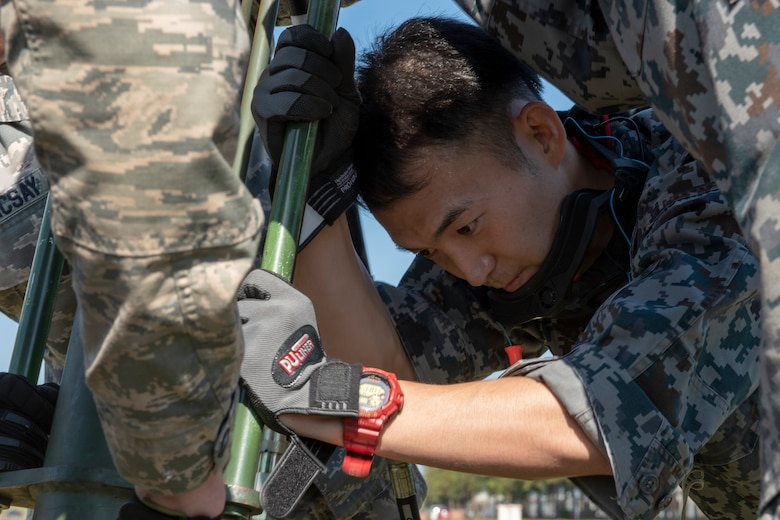 A member of the Koku Jietai (Japan Air Self-Defense Force) works with the Airmen from the 374th Civil Engineer Squadron to secure the Mobile Aircraft Arresting System (MAAS) in place at a bilateral training event at Yokota Air Base, Japan, Oct. 25, 2018.