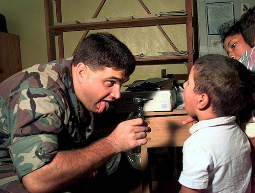 U.S. Air Force Capt. (Dr.) Cody Henderson, a pediatrician assigned to a 24th Medical Group Medical Readiness Training Exercise Team, examines a boy in a temporary field hospital in the Honduran village of Campo II, November 1998. U.S. joint-service medical teams drove into the Honduran countryside daily to treat people effected by Hurricane Mitch. (U.S. Army photo by Spc. Jeremy Ausburn)