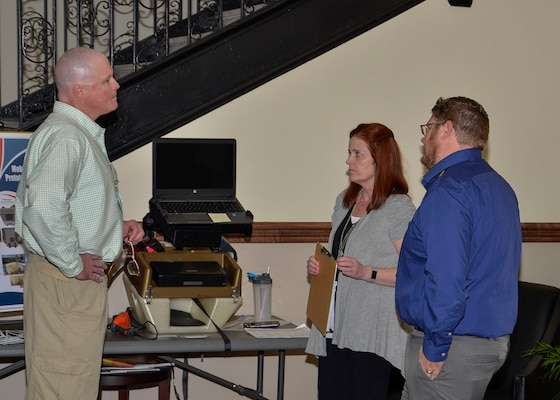 Kristy McNally (center) discusses the mobile work station's features with two summit attendees.