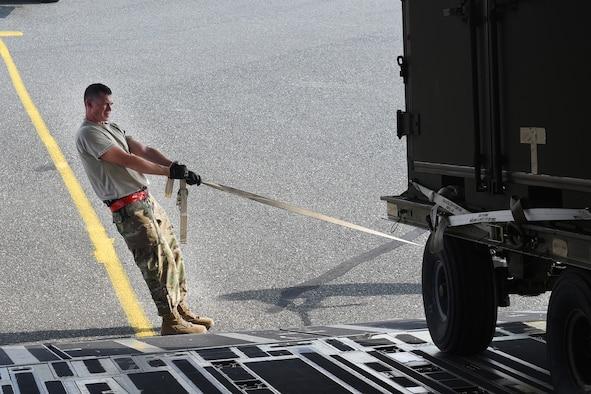 Airmen unload cargo from a C-17