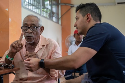 Juan Francisco Saerz, a medical student from Quito, Ecuador, helps a patient find the correct eye-glasses prescription.