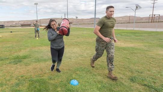 Sgt. Benjamin Crouch, Supply Administrator, runs with his wife, Blanca Crouch, during the Combat Fitness Test event during Jane Wayne Day aboard Marine Corps Logistics Base Barstow, Calif., Oct. 12. 
