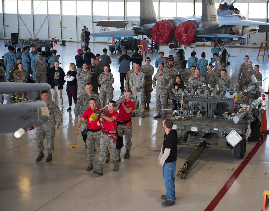 Image of Members of the 389th Fighter Squadron lift a munition to take to their jet during a weapons loading competition, Oct. 18, 2018, at Mountain Home Air Force Base, Idaho. The purpose of the competition is to simulate pressures of a deployed environment and instill pride and morale. (U.S. Air Force photo by Senior Airman Alaysia Berry)