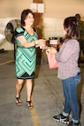 """Josielyn Williams, material handler, Fleet Support Division, accepts the first place prize from Samantha Atkinson, management and program analyst, in the annual FSD Chili Cook-Off at warehouse 406 aboard the Yermo Annex of Marine Corps Logistics Base Barstow. Williams' chili creation """"Sriracha """" earned her a $50 Visa gift card and some other goodies. The event raises money for the FSD Employee Appreciation Day activities."""