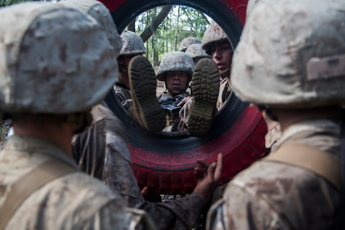 Recruits with Mike Company, 3rd Recruit Training Battalion, put a recruit through a tire during the Crucible on Marine Corps Recruit Depot Parris Island, S.C., Oct. 18, 2018. The Crucible is a 54-hour culminating event that requires recruits to work as a team and overcome challenges in order to earn the title United States Marine. (U.S. Marine Corps photo by Lance Cpl. Andrew Neumann)