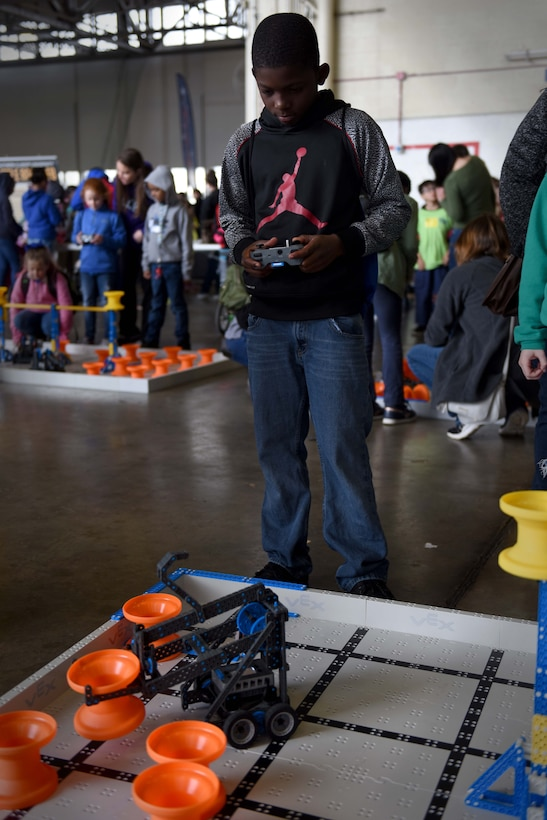 A Student in jeans and a gray sweater uses a robot to move orange cones.
