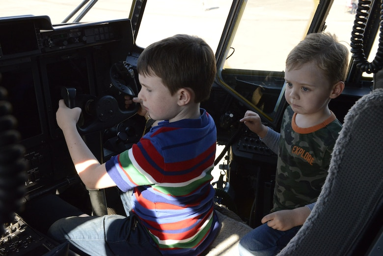Children sit inside the flight deck of an aircraft