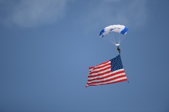 A parachutist glides down after jumping out of an aircraft holding an American flag during an air show