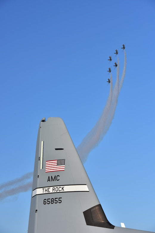 A group of U.S. Air Force Thunderbirds fly in formation around a C-130 from Little Rock