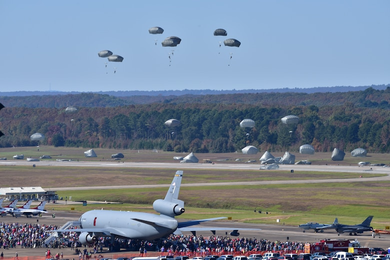 Parachutists glide from the sky onto a flightline during an airshow