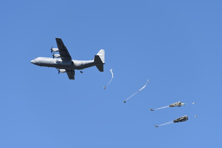 A gray C-130 drops parachutists mid air