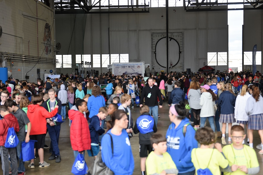 A crowd of school age children gather in an aircraft hangar