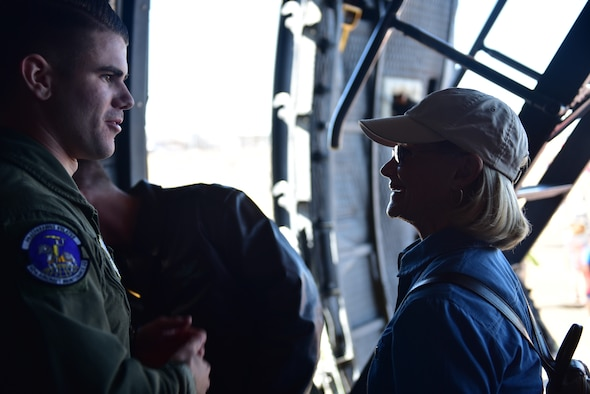 A male speaks to a female on an aircraft during an air show