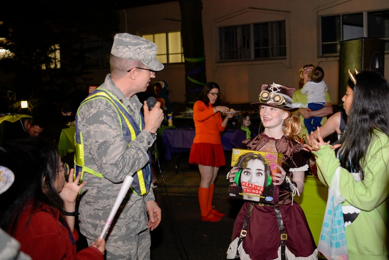 Maj. Kelly Stahl, 374th Airlift Wing chaplain, presents a prize to an event goer during Trunk-or-Treat, Oct. 26, 2018, at Yokota Air Base, Japan.