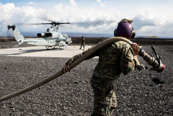 Marine Corps Cpl. Garrett Subik, a bulk fuel specialist with Marine Wing Support Detachment 24, moves a fuel line toward a landing pad in order to start fueling a AH-1W Super Cobra helicopter during a field test for an Expeditionary Mobile Fuel Additization Capability system as part of the Rim of the Pacific exercise at Pohakuloa Training Area, Hawaii.