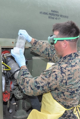 Marine Corps Sgt. Andrew Grable examines a sample of fuel before conducting laboratory testing to ensure it meets military specifications. The Marines tested a prototype Expeditionary Mobile Fuel Additization Capability during the Rim of the Pacific exercise.