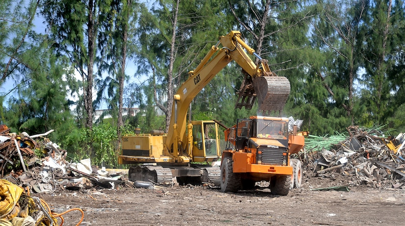 Operators use heavy equipment to load and transport millions of pounds of scrap material to heavy barges that will take it away for sorting and recycling in the city of Majuro in the Marshall Islands.