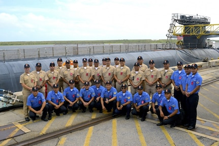 Crew members from the Peruvian submarine BAP Arica (SS-36) pose for group photos in front of the Ohio-class ballistic missile submarine USS Maryland