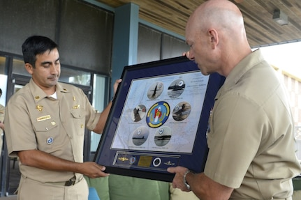 Capt. Robert Wirth, commodore of Submarine Squadron 20, presents Cmdr. Enrique Vargas, captain of Peruvian Submarine BAP Arica (SS-36), with a commemorative photo of the Kings Bay submarine fleet.