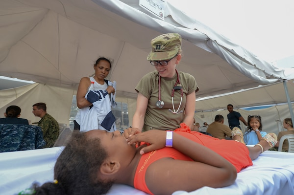 Army Capt. Christin Folker treats a patient in Ecuador.