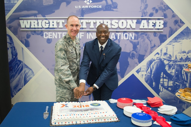 Col. Leonard T. Rose, 88th Mission Support Group commander, and Jermaine Wilson, Wright-Patterson Exchange general manager, cut a commerative cake at the Exchange's grand re-opening ceremony Oct. 25, 2018.