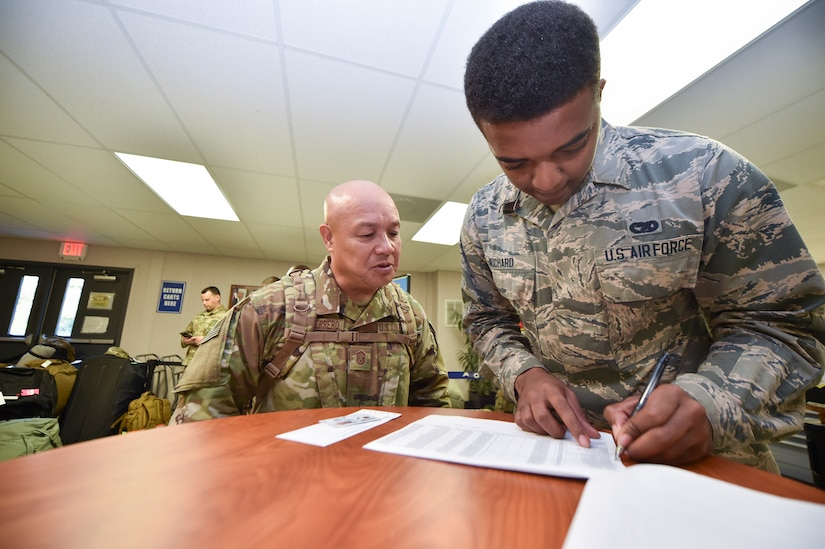 Airman 1st Class Malik Richard, 437th Aerial Port Squadron passenger operations technician, verifies a passenger's credentials as they move through a security checkpoint as part of a mission to deploy service members through Joint Base Charleston Oct. 15, 2018.