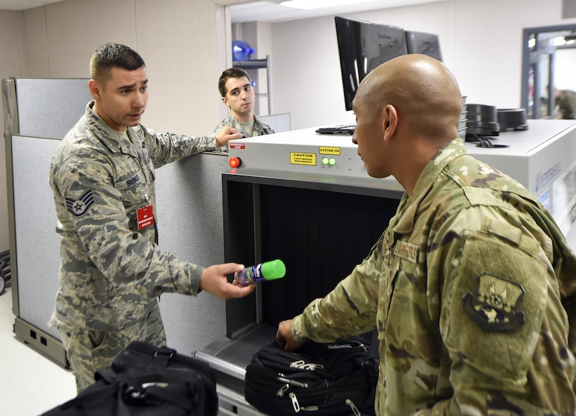 Staff Sgt. James Barker, 437th Aerial Port Squadron passenger operations supervisor, removes an unauthorized item from a bag at a security checkpoint Oct. 15, 2018.