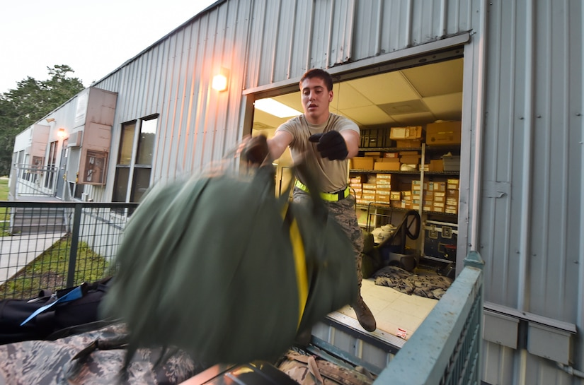 Airman 1st Class Brett Petraitis, 437th Aerial Port Squadron passenger operations technician, stacks bags into a container to be transported to the Joint Base Charleston flightline Oct. 15, 2018.