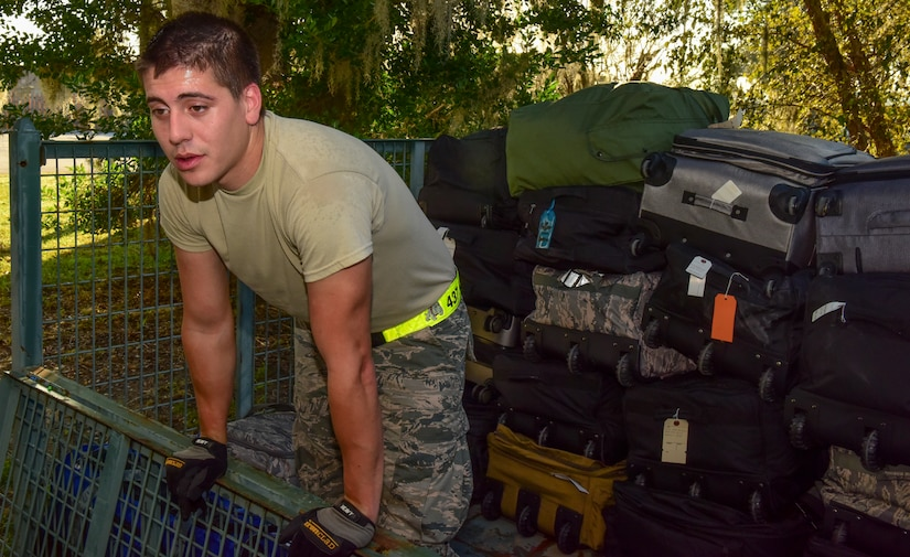 Airman 1st Class Brett Petraitis, 437th Aerial Port Squadron passenger operations technician, waits to be handed the next bag as he stacks them for transportation to the Joint Base Charleston flightline Oct. 15, 2018.
