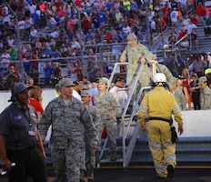 Members of the 932nd Airlift Wing and other active duty Airmen cross over the track safety barrier after helping take part in the national anthem ceremony at Gateway track.  As part of the event, 932nd Airlift Wing Maintenance Group commander, Col. Sharon Johnson, was recognized on stage with the Indy drivers at the Bommarito Automotive Group 500 Aug. 25, 2018, Gateway Motorsports Park, Madison, Illinois. Johnson was an honored VIP to help kick off the 2nd annual IndyCar race which was won by Will Power.  The 932nd Airlift Wing was represented by maintenance, medical, public affairs staff and operations personnel.  (U.S. Air Force photo by Lt. Col. Stan Paregien