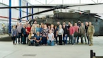 Group of people stand in front of helicopter inside hangar.