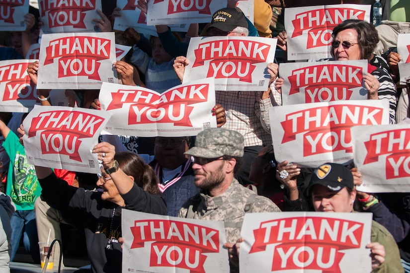 Crowd holds up several thank you signs.