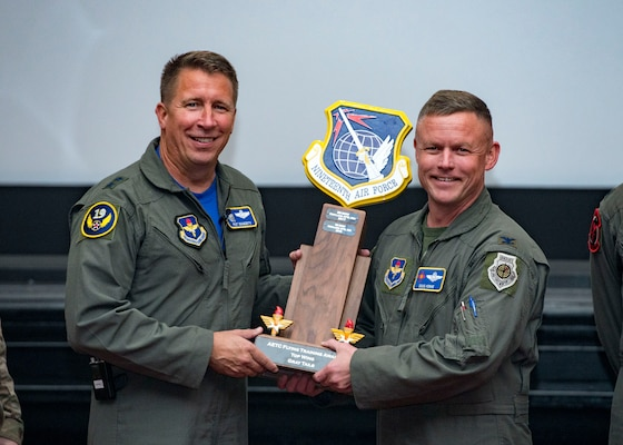 Maj. Gen. Patrick Doherty, 19th Air Force commander, presents the Top Wing-Gray Tail Division Award to Col. Doug Horne, 58th Special Operations Wing, during the Air Education and Training Command Flying Training Awards Ceremony Oct. 26, 2018, at Joint Base San Antonio-Randolph, Texas. The award ceremony recognizes individuals, squadrons, groups and wings whose efforts have led to the highest levels of student production.