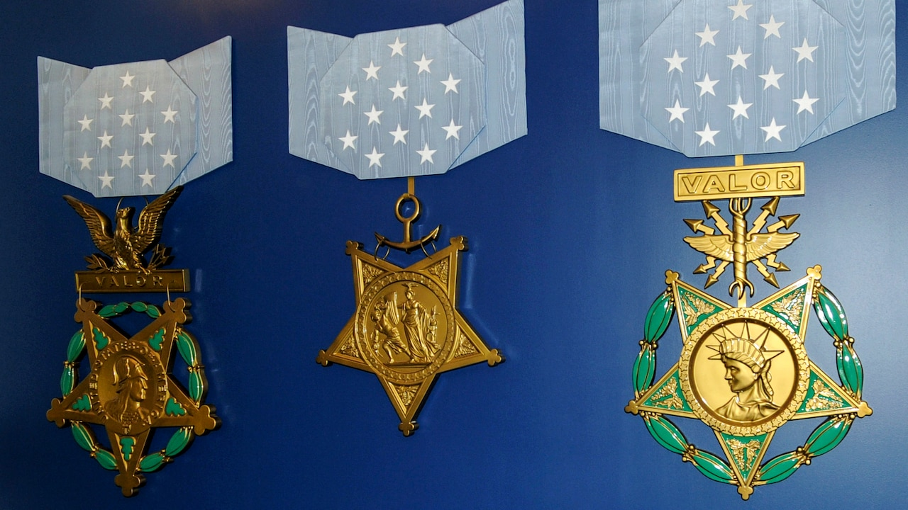 Three large recreations of Medals of Honor are displayed on a blue wall.