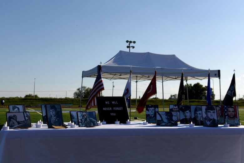A Prisoners of War and Missing in Action memorial at the track on Goodfellow Air Force Base, Texas, Oct. 26, 2018. Photos on the table honor Texans declared as POWs or MIA.  (U.S. Air Force photo by Senior Airman Randall Moose/Released)