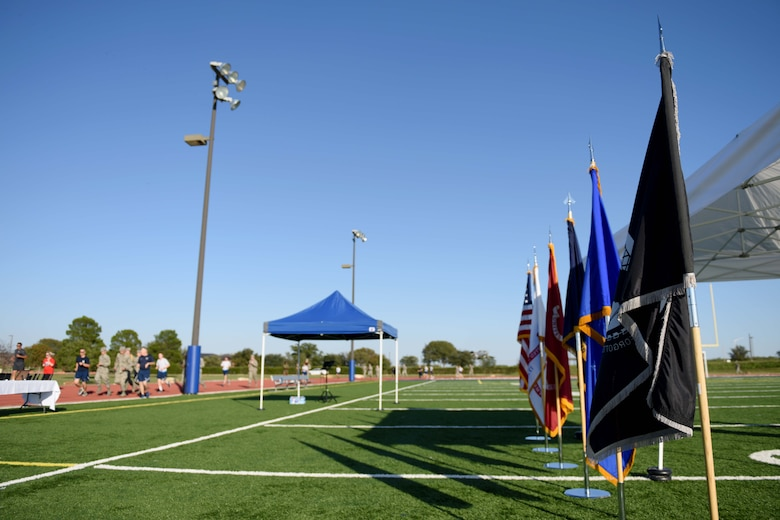 Participants run past the American flag, military service flags and a Prisoners of War and Missing in Action flag during the 24-hour Prisoners of War and Missing in Action Vigil at the track on Goodfellow Air Force Base, Texas, Oct. 26, 2018. Congress ordered prominent display of the POW/MIA flag on POW/MIA Recognition Day and several other national observances, including Armed Forces Day, Memorial Day, Flag Day, Independence Day and Veterans Day. (U.S. Air Force photo by Senior Airman Randall Moose/Released)
