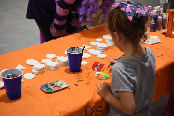 A child paints a ceramic pumpkin during the kid's carnival at Ghoulfellow in the Louis F. Garland Department of Defense Fire Academy on Goodfellow Air Force Base, Texas, Oct. 27, 2018. Booths were set up in the High Bay with carnival games for children to play. (U.S. Air Force photo by Airman 1st Class Zachary Chapman/Released)