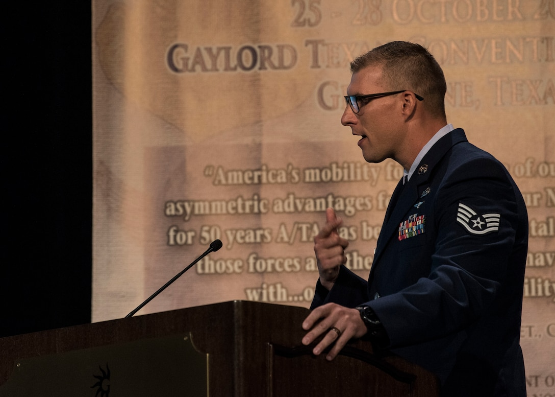 Staff Sgt. Travis Alton from the 19th Logistical Readiness Squadron briefs his design of an M-1 cargo parachute release assembly time block fair safe during the 2018 AMC Phoenix Spark Tank competition, where four finalists pitched their innovation ideas to a panel of judges at the