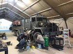 Vehicle maintainers assigned to the 724th Expeditionary Air Base Squadron work on a P-18 Combat Fire Truck radiator at Nigerien Air Base 201, Niger, Oct. 16, 2018. The maintainers were able to create a fix for the leaky radiator and return it to the fleet in three days. (Courtesy photo)
