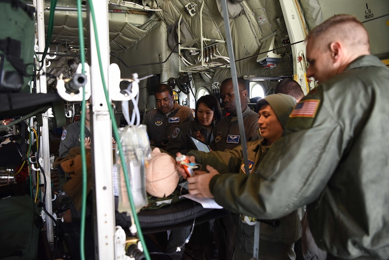 Members of the 86th Aeromedical Evacuation Squadron huddle around a medical dummy to practice clinical skills on a C-130J Super Hercules aircraft, Oct. 23, 2018. 86th AES train on an aircraft to make sure all crewmembers can fly safe, take care of patients, and are efficient in their clinical skills.
