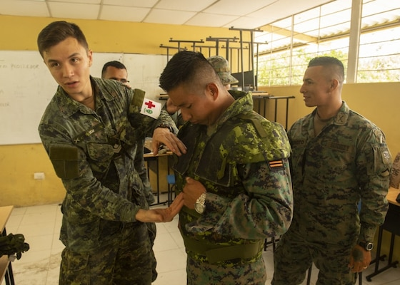 Canadian Forces Master Corporal Kristian Tam, discusses field medicine techniques during a multi-nation information exchange meeting on medicine in a tactical environment with American and Ecuadorian service members.