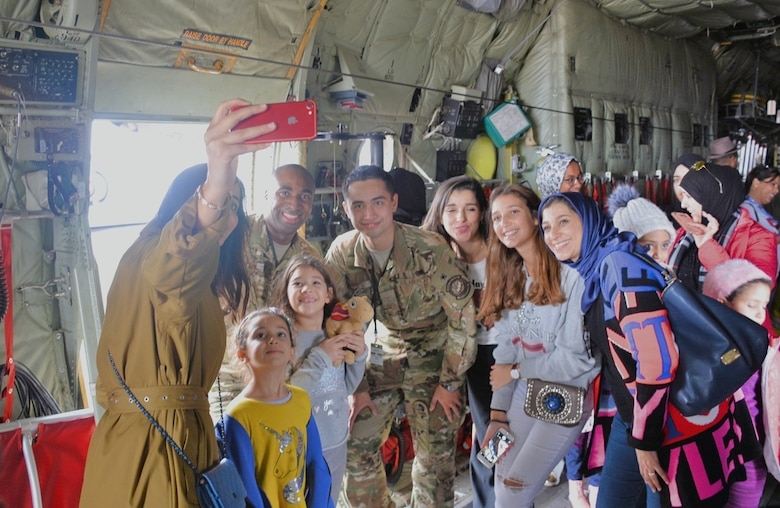 C-130 crewmembers SSgt Mario Linton (left) and A1C Alex Loberg from the 86th Airlift Wing, Ramstein Air Force Base, Germany, pose for a pictures with visitors at the Marrakech Air Show in Marrakech, Morocco. The air show drew hundreds of civilian and military aviation leaders and thousands of public visitors Oct. 24-27 to showcase leadership in aerospace technologies by the U.S., Morocco and other regional partners. Continued U.S participation in the Marrakech Air Show, held every two years since 2008, promotes strong ties with Morocco and demonstrates to large audiences that U.S. industry is producing the types of equipment that is critical to current and future military operations.