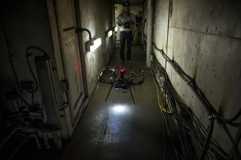 Student-researcher from Carnegie Mellon University remotely maneuvers quadrotor micro-air vehicle through narrow hallways of Naval Research