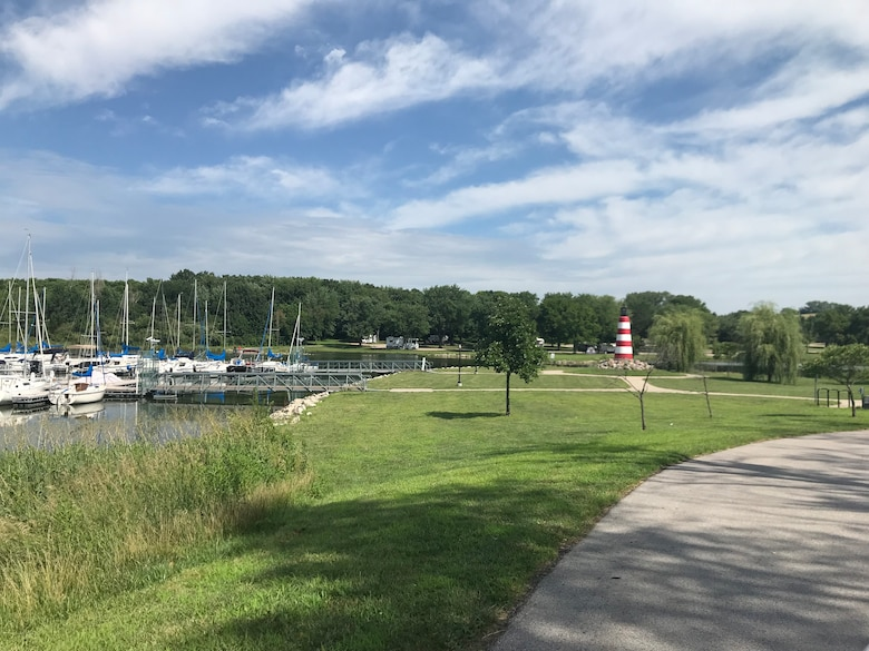 A view of Cunningham Lake Jul. 18, 2018, located in Omaha, Nebr. (Photo by Angel Pletka, USACE). Boats appear in the left of the photo, stationary in the lake. A path leads forward, in the right of the photo.