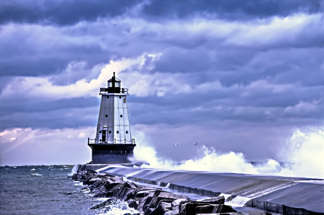 Ludington Lighthouse with waves crashing over the break wall and storm clouds rolling overhead. Ludington, Michigan.