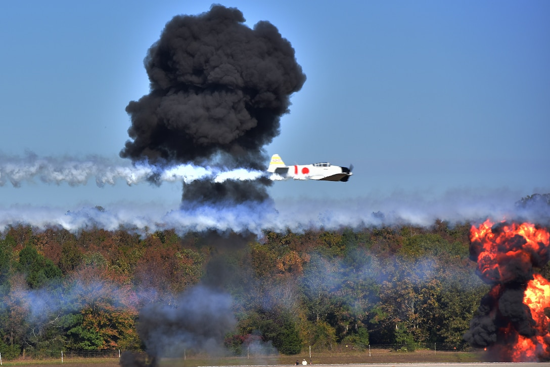 Japanese Zero aircraft fly's over mock explosions simulating attack runs from left to right.