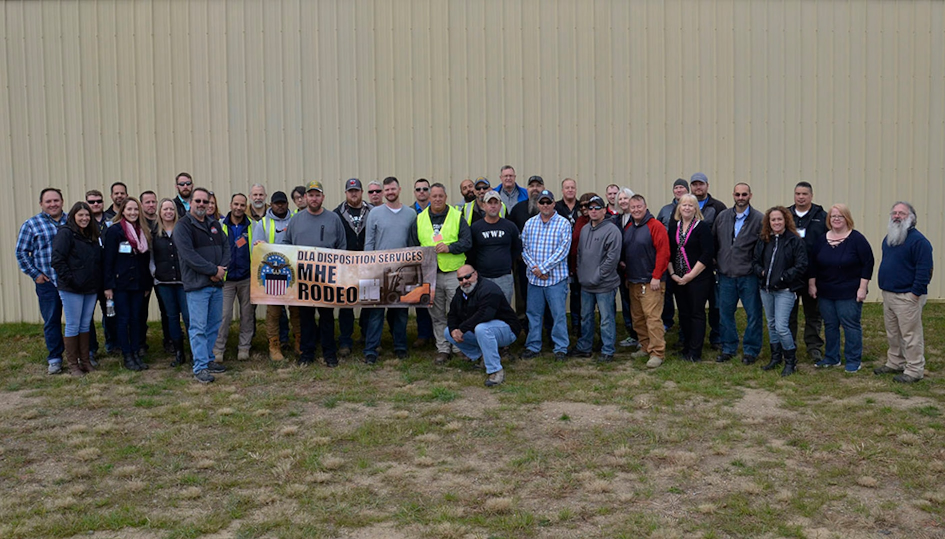 MHE Rodeo competitors, judges and support volunteers pose at the Battle Creek Air National Guard Base in Michigan where the inaugural competition pitted 13 of the agency's best fork truck drivers from around the globe Oct. 23-25.