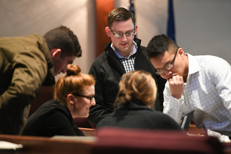Attendees, including military members in civilian attire, at the 2018 Hanscom Air Force Base Revolutionary Acquisition Techniques, Procedures and Collaboration (RATPAC) Fractal event pore over a challenge problem, Oct. 25, in the Hanscom Conference Center, Hanscom Air Force Base, Mass. Organizers said business casual clothes encouraged attendees to freely exchange of ideas during the academic challenge portion. (U.S. Air Force photo by Todd Maki)