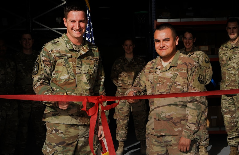 Airman 1st Class Dustin Marin, left, 379th Expeditionary Logistics Readiness Squadron materiel management technician, and Staff Sgt. Mario Lopez, right, 379th ELRS materiel management craftsman, cut a ribbon during the opening of the new Desert Depot Oct. 30, 2018, at Al Udeid Air Base, Qatar. The ceremony completes a two-year effort to relocate to a $1.1 million facility. Airmen of the 379th ELRS pulled together to move 42,000 assets to the new location during a four-day period. (U.S. Air Force photo by Tech. Sgt. Christopher Hubenthal)