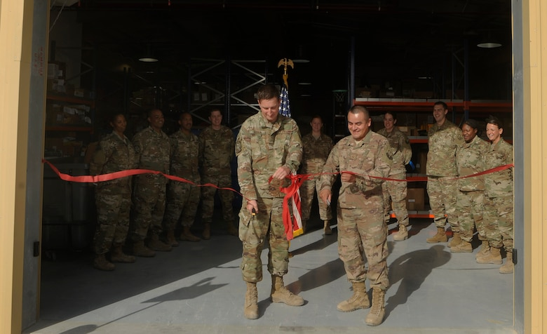 Airman 1st Class Dustin Marin, left, 379th Expeditionary Logistics Readiness Squadron materiel management technician, and Staff Sgt. Mario Lopez, right, 379th ELRS materiel management craftsman, cut a ribbon during the grand opening of the new Desert Depot Oct. 30, 2018, at Al Udeid Air Base, Qatar. The ceremony completes a two-year effort to relocate to a $1.1 million facility. Airmen of the 379th ELRS pulled together to move 42,000 assets to the new location during a four-day period. (U.S. Air Force photo by Tech. Sgt. Christopher Hubenthal)